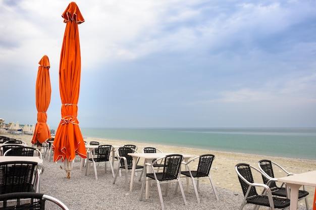 Cafetería de playa con mesas y sillas vacías.