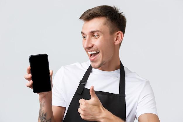 Cafetería y restaurantes, propietarios de cafeterías y concepto minorista. vendedor guapo alegre, mirando la pantalla del teléfono móvil impresionado, como una nueva aplicación o página web que muestra el pulgar hacia arriba en señal de aprobación