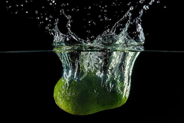 Caída de aguacates en el agua, rociado para el diseño, congelación en movimiento. salpicaduras de agua y verduras