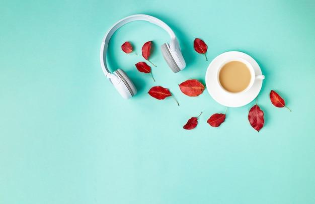 Caída de composición plana con hojas de otoño rojas, taza de café y auriculares blancos sobre fondo azul. fondo de podcast de otoño. concepto de lista de reproducción de otoño.