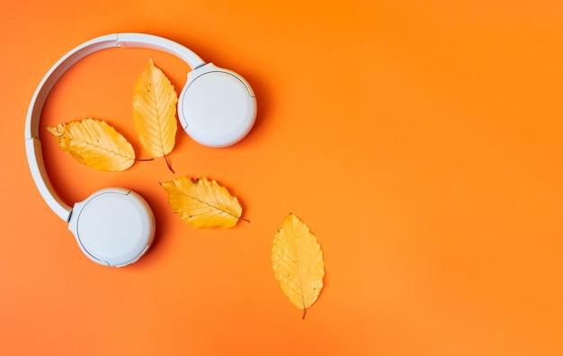 Caída de composición plana con hojas realistas y auriculares blancos sobre fondo naranja. fondo de podcast de otoño. concepto de lista de reproducción de otoño.