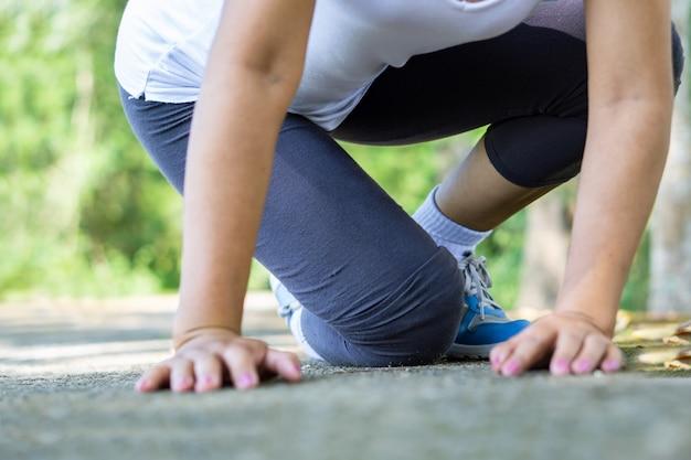 Caída femenina y dolor de rodilla durante el deporte.
