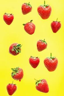 Caída de fresa aislado sobre fondo amarillo, enfoque selectivo