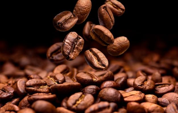 Caída de los granos de café. fondo oscuro con espacio de copia