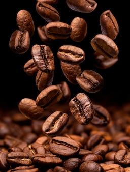 Caída de granos de café. oscuro con espacio de copia