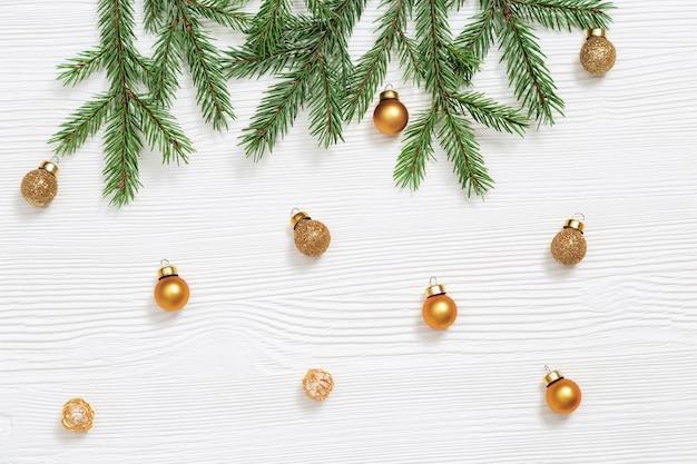 Caída de juguetes dorados metálicos, pequeñas bolas brillantes, ramas de abeto verde natural