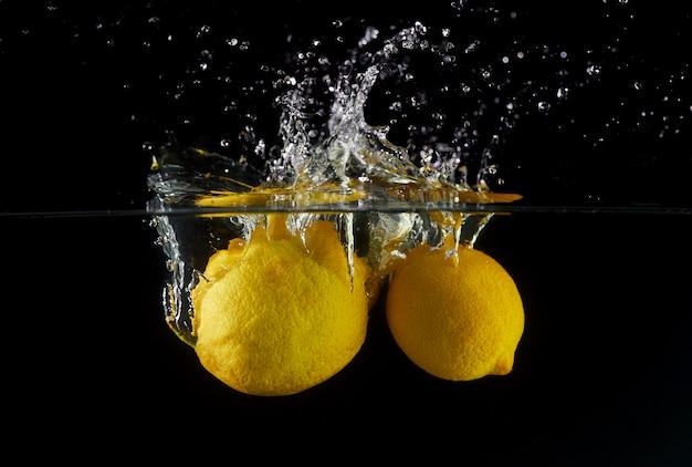 Caída de limones en agua, spray para diseño, congelación en movimiento. salpicaduras de agua y verduras aisladas en negro