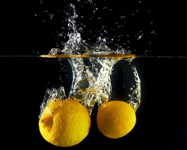 Caída de limones en agua, spray para diseño, congelación en movimiento. salpicaduras de agua y verduras