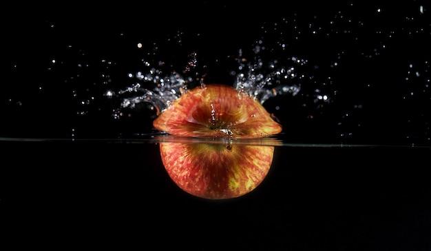 Caída de manzana al agua, rociado para el diseño, congelación en movimiento. salpicaduras de agua y verduras