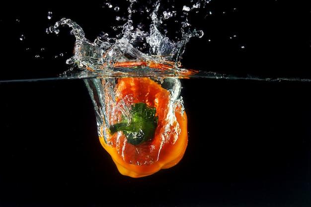 La caída de la pimienta búlgara de naranja dulce en agua, spray para el diseño, congelación en movimiento. salpicaduras de agua y verduras aisladas en negro
