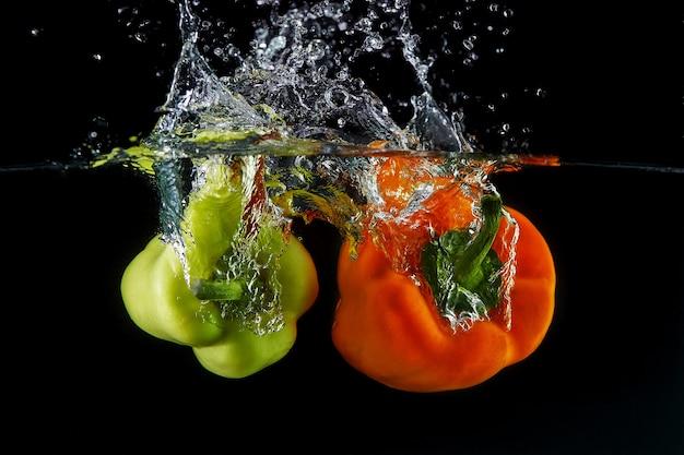 Caída de pimientos búlgaros de naranja dulce y verde en el agua, rociado para el diseño, congelación en movimiento. salpicaduras de agua y verduras aisladas