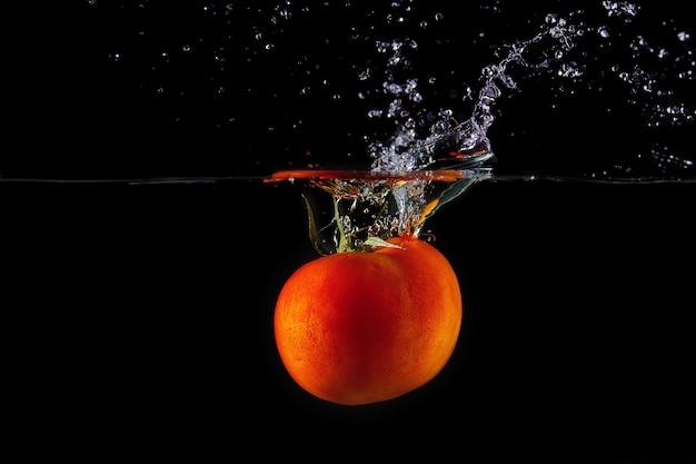 Caída de tomate con una cola verde en el agua, rocíe para el diseño, congelación en movimiento. salpicaduras de agua y verduras aisladas en negro