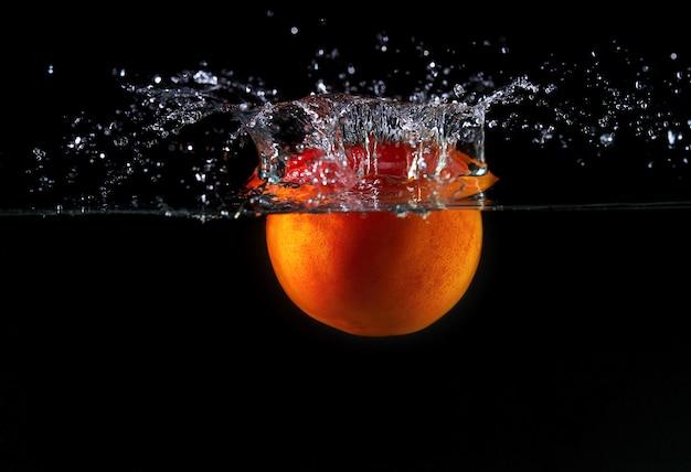 Caída de tomate con una cola verde en el agua, rocíe para el diseño, congelación en movimiento. salpicaduras de agua y verduras