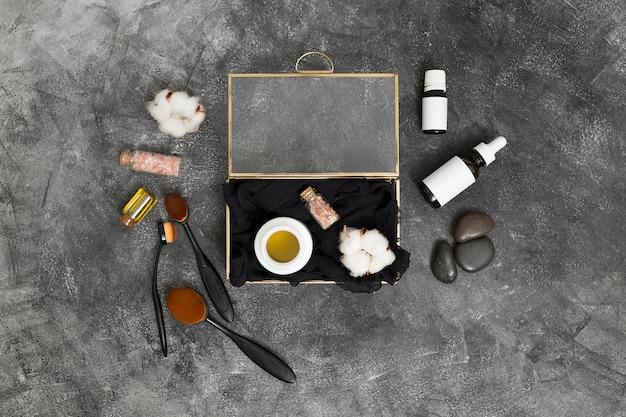 Una caja abierta con miel; sal de himalaya rosa y capullo de algodón con productos cosméticos sobre fondo negro de concreto