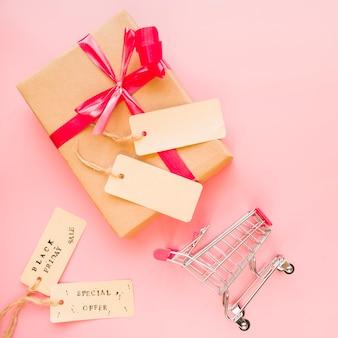 Caja actual con lazo rojo cerca de carrito de compra y etiquetas de venta