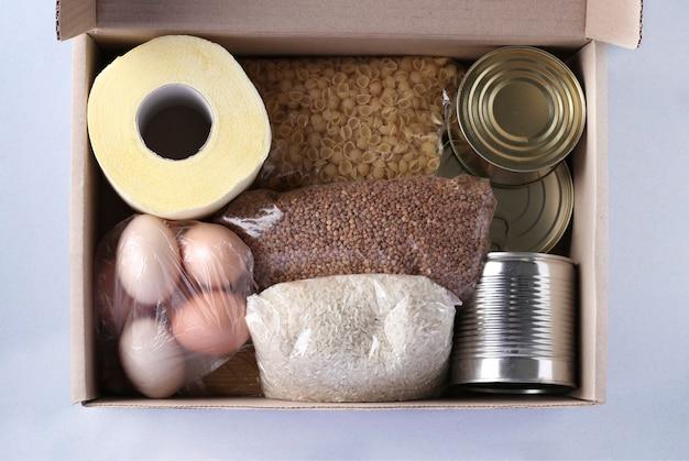 Caja con alimentos sobre fondo azul claro. arroz, trigo sarraceno, pasta, conservas, papel higiénico, huevos. entrega de comida, donación, vista desde arriba