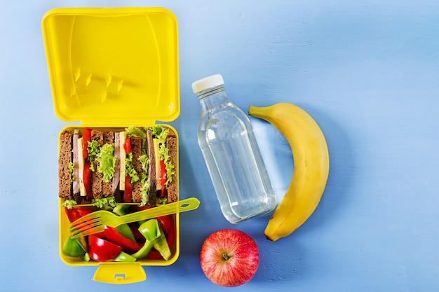 Caja de almuerzo escolar saludable con sándwich de carne y verduras frescas, botella de agua y frutas.