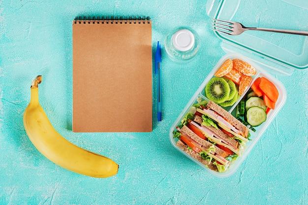 Caja de almuerzo escolar con sándwich, verduras, agua y frutas en la mesa.