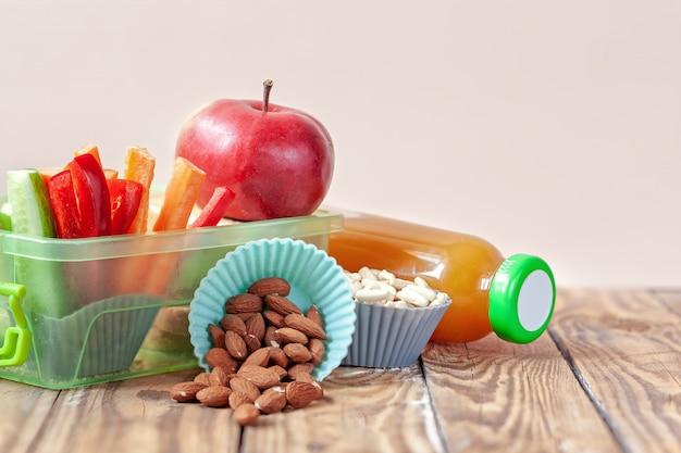 Caja de almuerzo escolar con sandwich, verduras, jugo y almendras en la mesa.