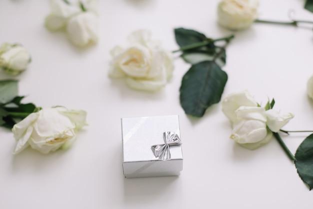 Caja de anillo de joyería de plata y rosas blancas, amor de boda, propuesta de día de san valentín, concepto de feliz cumpleaños