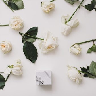 Caja de anillo de joyería y rosas blancas sobre blanco