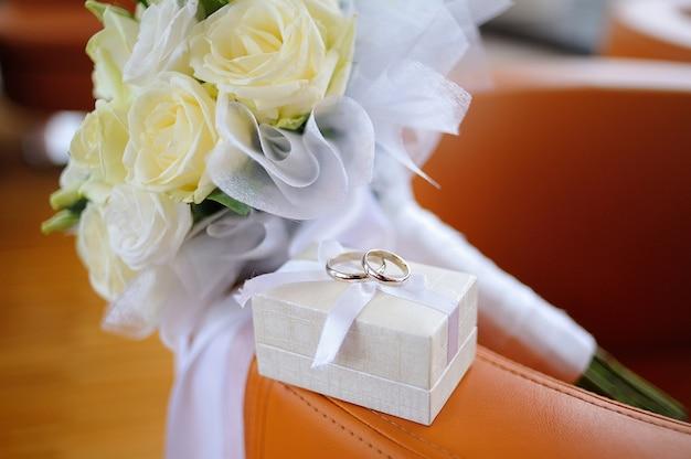 Caja con anillos de bodas de oro y un ramo de rosas blancas.