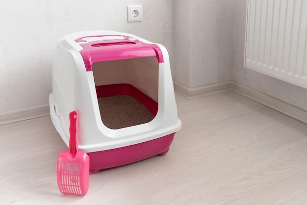 Caja de arena para gatos rosa con pala en la habitación