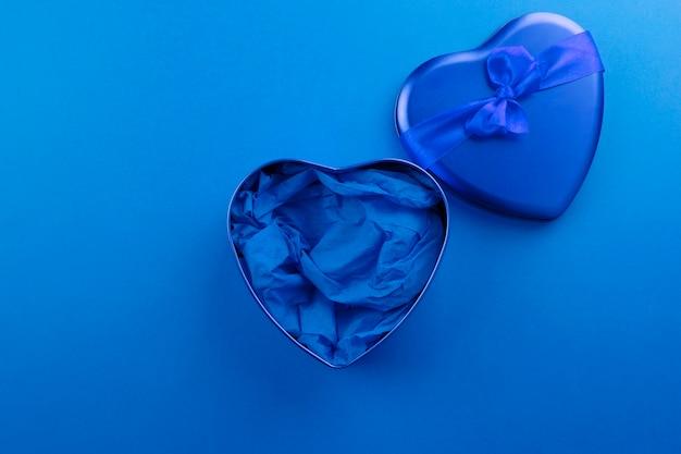 Caja azul en forma de corazón con cinta sobre fondo azul.