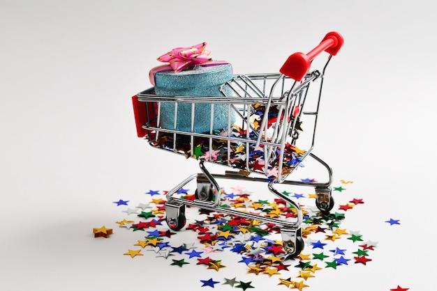 Caja azul presente con lazo rosa en un carrito de compras y confeti sobre un fondo blanco.
