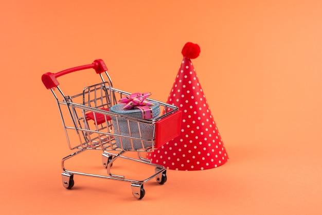Caja azul presente con lazo rosa en un carrito de compras y gorra de cumpleaños sobre un fondo rojo.