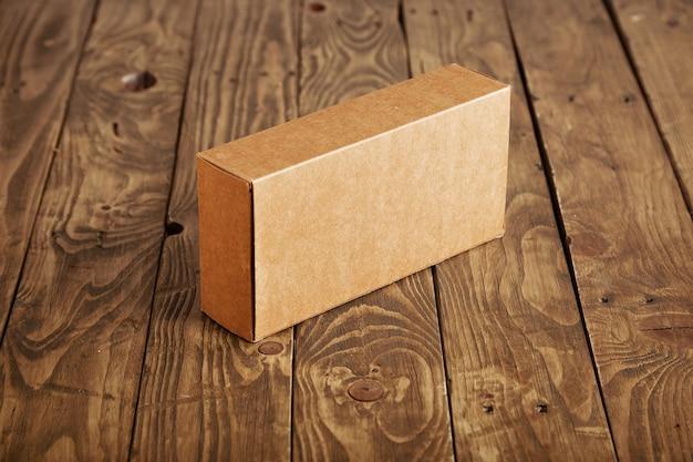 Caja de cartón artesanal presentada en mesa de madera cepillada acentuada