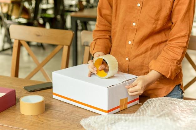 Caja de cartón de embalaje del propietario de la pequeña empresa de pequeña empresa en el lugar de trabajo.