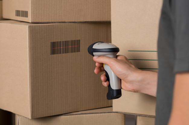 Caja de cartón de escaneo de mensajería con escáner de código de barras en el almacén