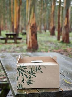 Caja de cartón con hojas verdes sobre una mesa de picnic de madera en un bosque con árboles en el fondo