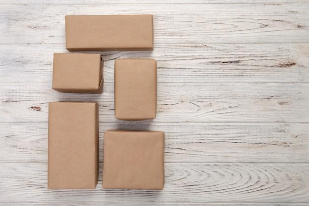 Caja de cartón en madera blanca, vista superior del paquete de correo marrón
