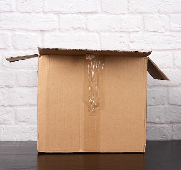 Caja de cartón marrón abierta sobre fondo de pared de ladrillo blanco