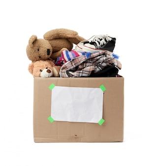 Caja de cartón marrón con cosas, juguetes aislados en blanco backgrou