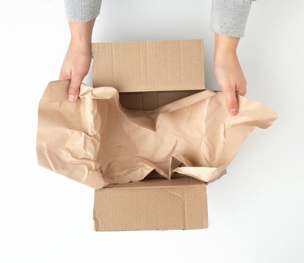 Caja de cartón marrón cuadrada abierta con papel arrugado marrón
