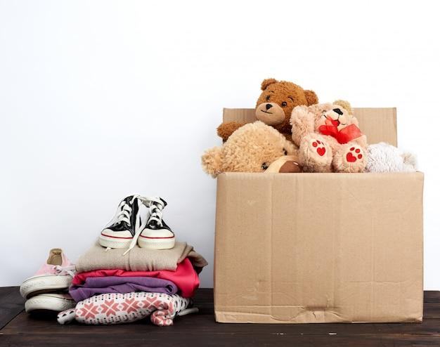 Caja de cartón marrón llena de cosas y juguetes para niños.