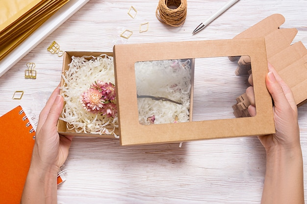 Caja de cartón marrón con relleno de papel triturado arrugado sobre mesa de madera