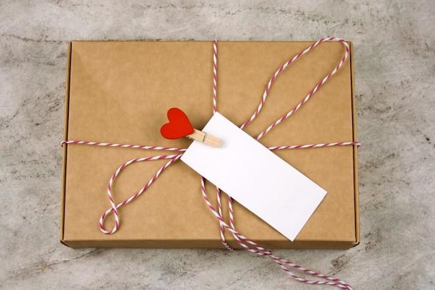 Caja de cartón con pin de tela con corazón rojo y etiqueta blanca vacía con lugar para texto de mármol