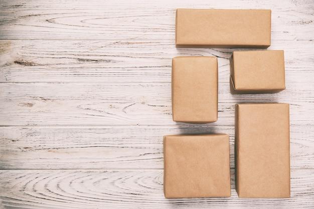 Caja de cartón sobre fondo blanco de madera, vintage, tonos marrón vista superior del paquete de correo