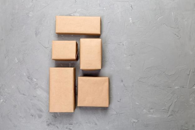 Caja de cartón sobre fondo de cemento gris, vista superior del paquete de correo marrón