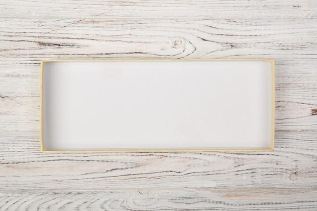 Caja de cartón vacía abierta con la cubierta en el fondo de madera blanco.