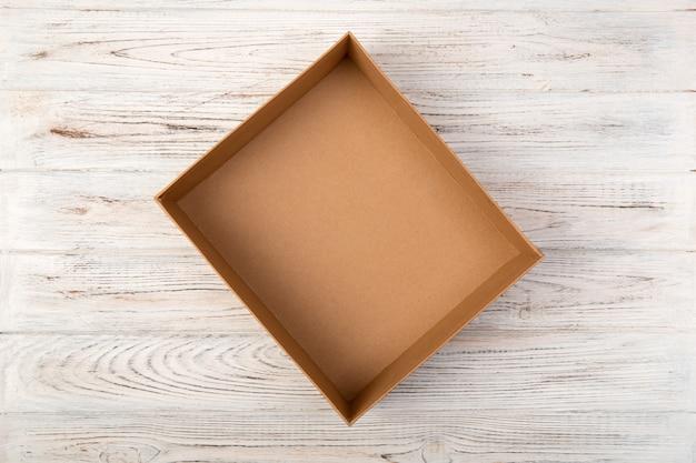Caja de cartón vacía en una vista superior de fondo de madera blanco