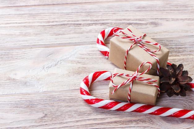 Caja casera con un lazo rojo cerca de bastones de caramelo de navidad