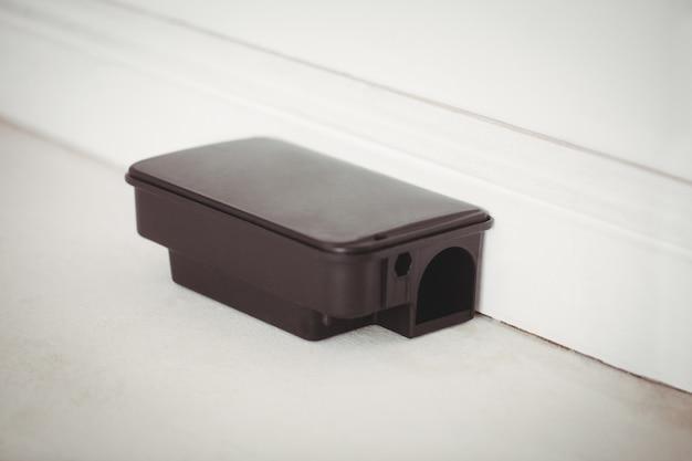 Caja de cebo para ratas en piso blanco en una casa