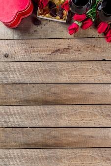 Caja de chocolate, rosas, copas de vino y corazón en mesa de madera