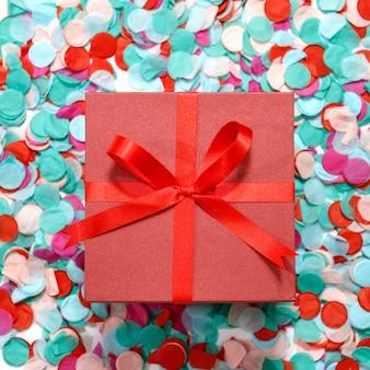 Caja y cinta rojas de regalo en la decoración colorida del confeti para la fiesta de cumpleaños. lay flat.