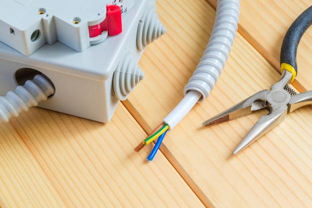 Caja de conexiones con cable y herramienta para reparar sistemas eléctricos.